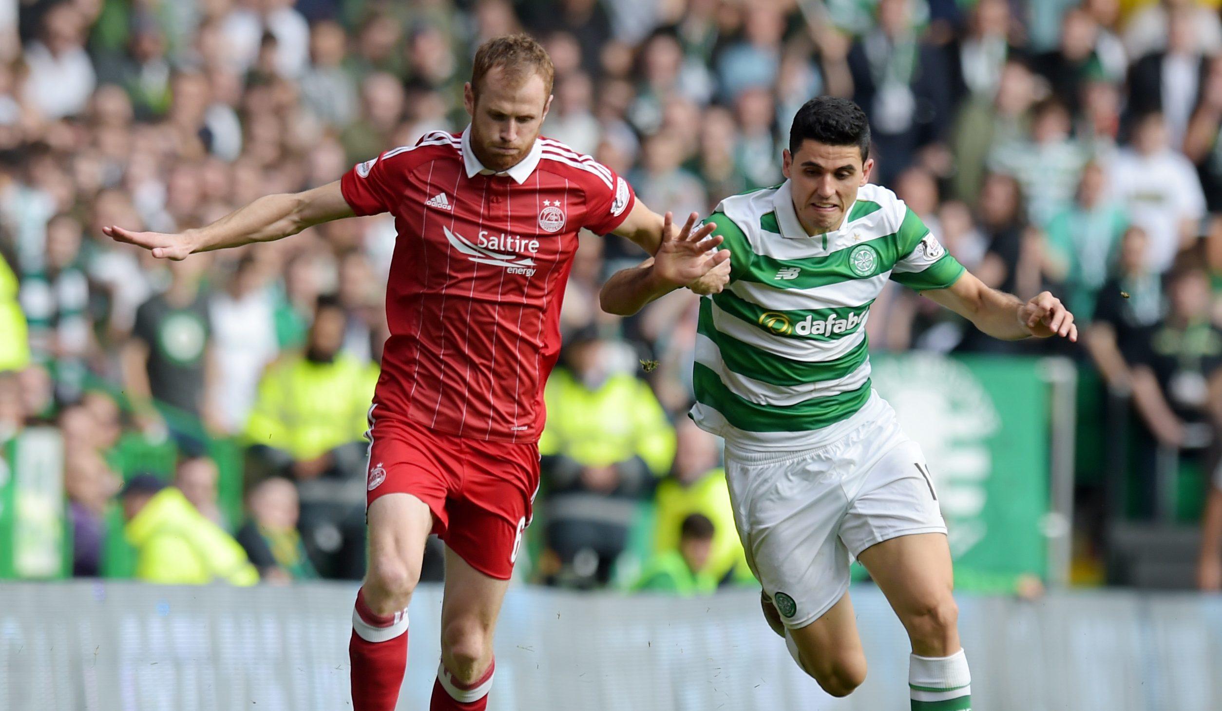 Aberdeen defender Mark Reynolds, left, holds off Celtic midfielder Tom Rogic.