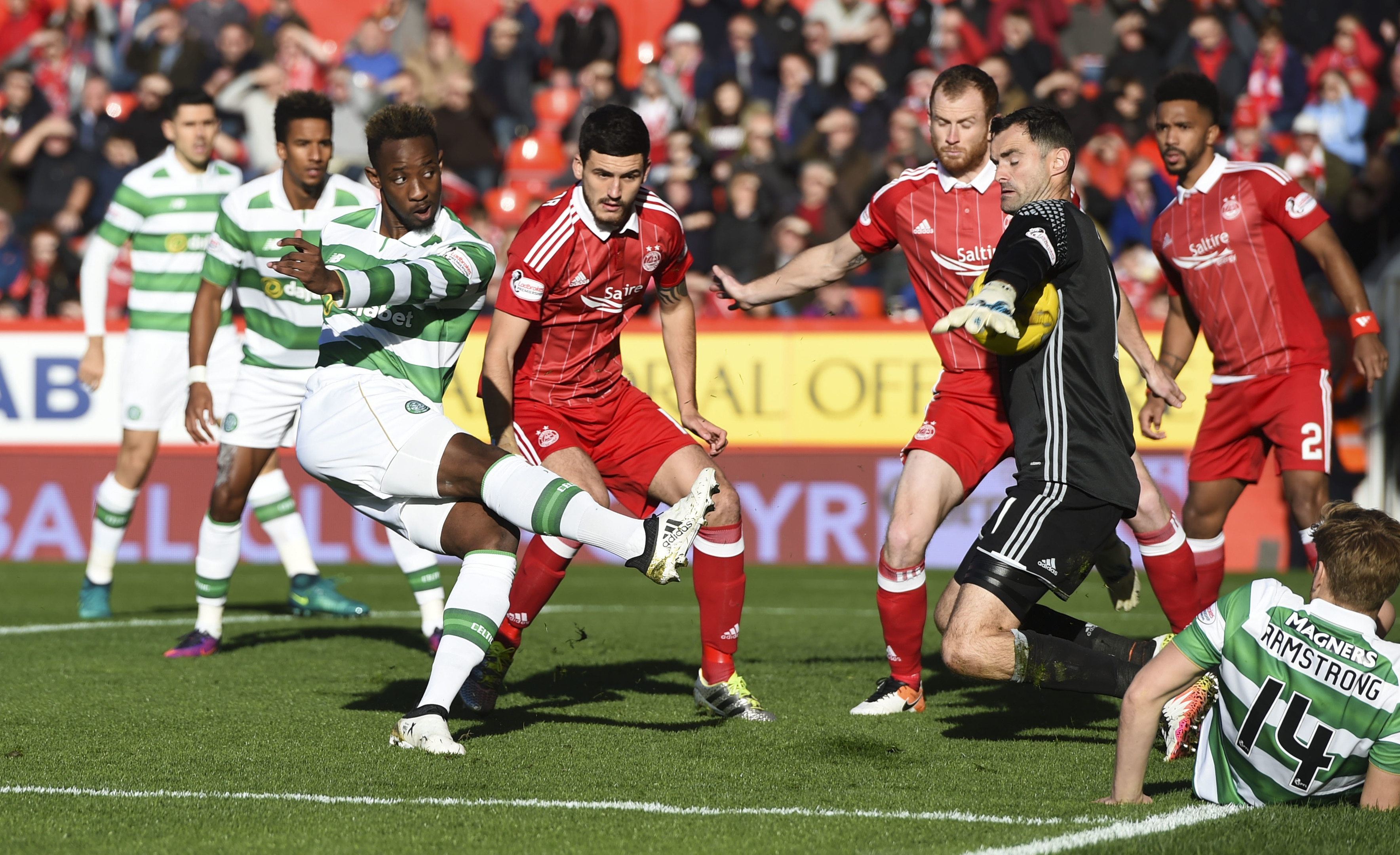 Dons goalie Joe Lewis saves a shot by Celtic's Moussa Dembele.