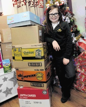 Kindhearted Beth stands next to a tower of supplies she has gathered.