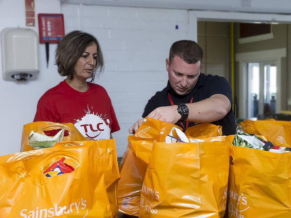 Tim McIlroy inspects donations with volunteer Sue Adlmam-Hill.