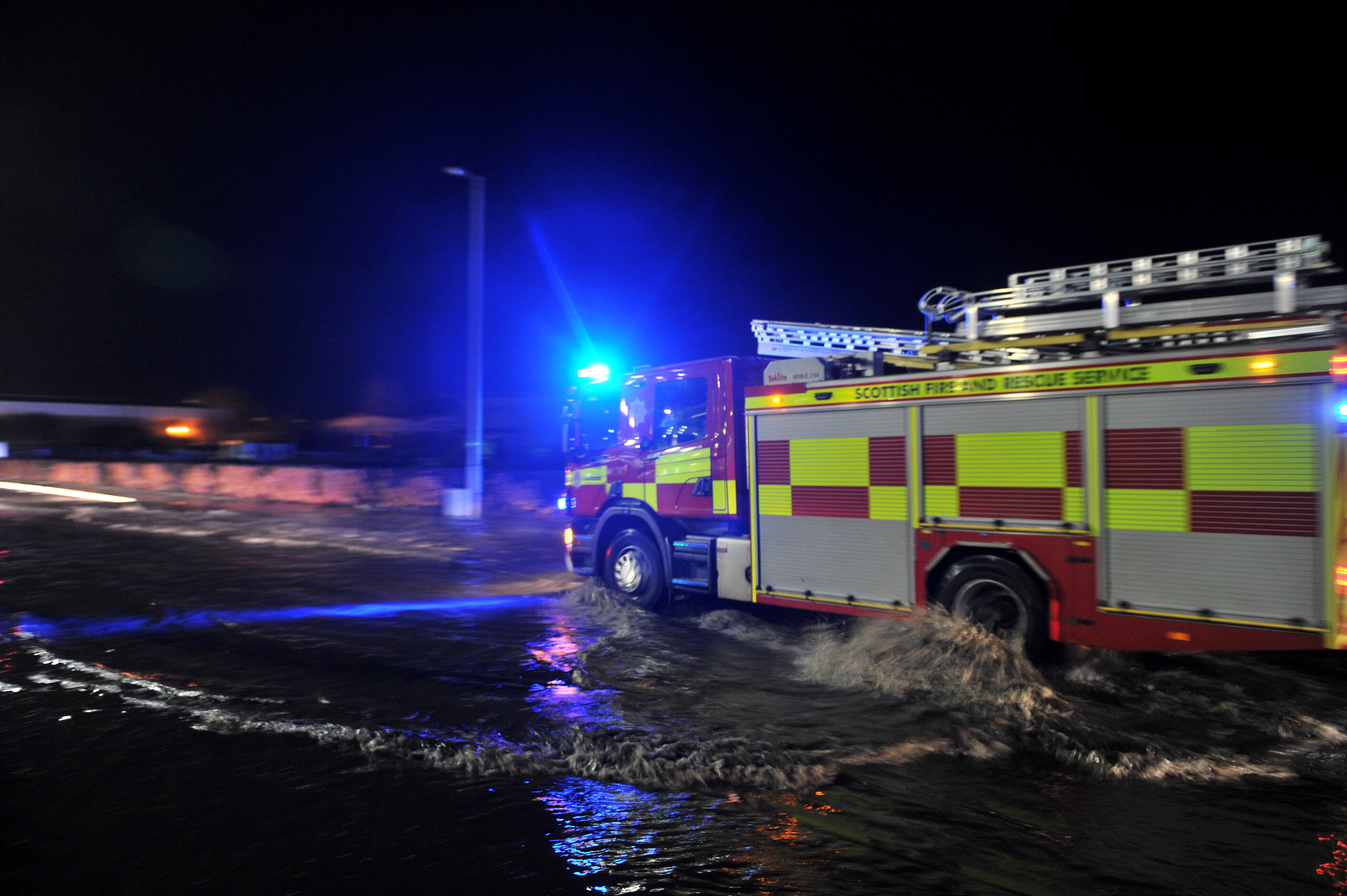 A fire service vehicle drives through flooding on Garthdee Road.