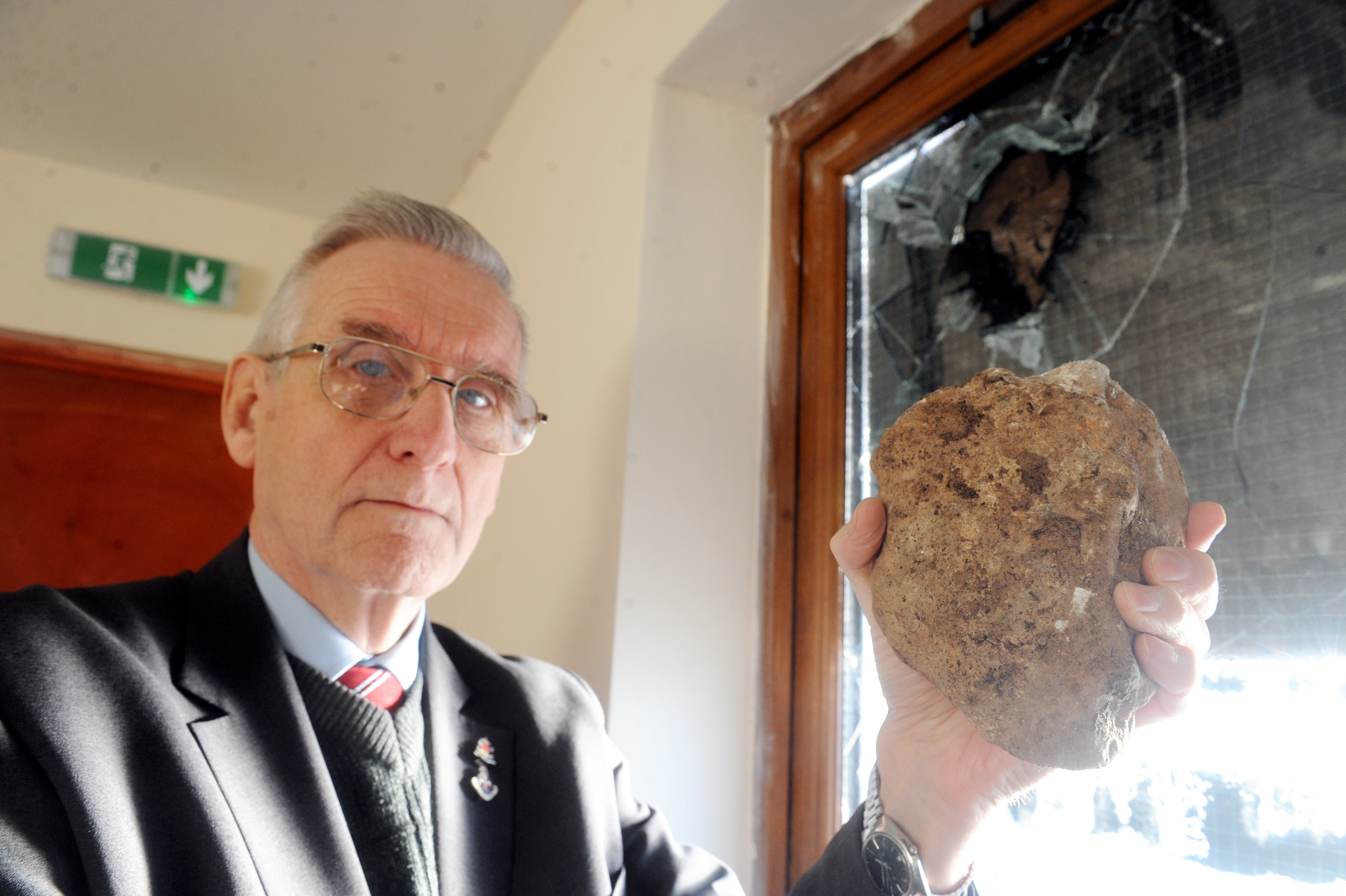 Rev Andy Cowie holds the rock which was hurled through the church window.