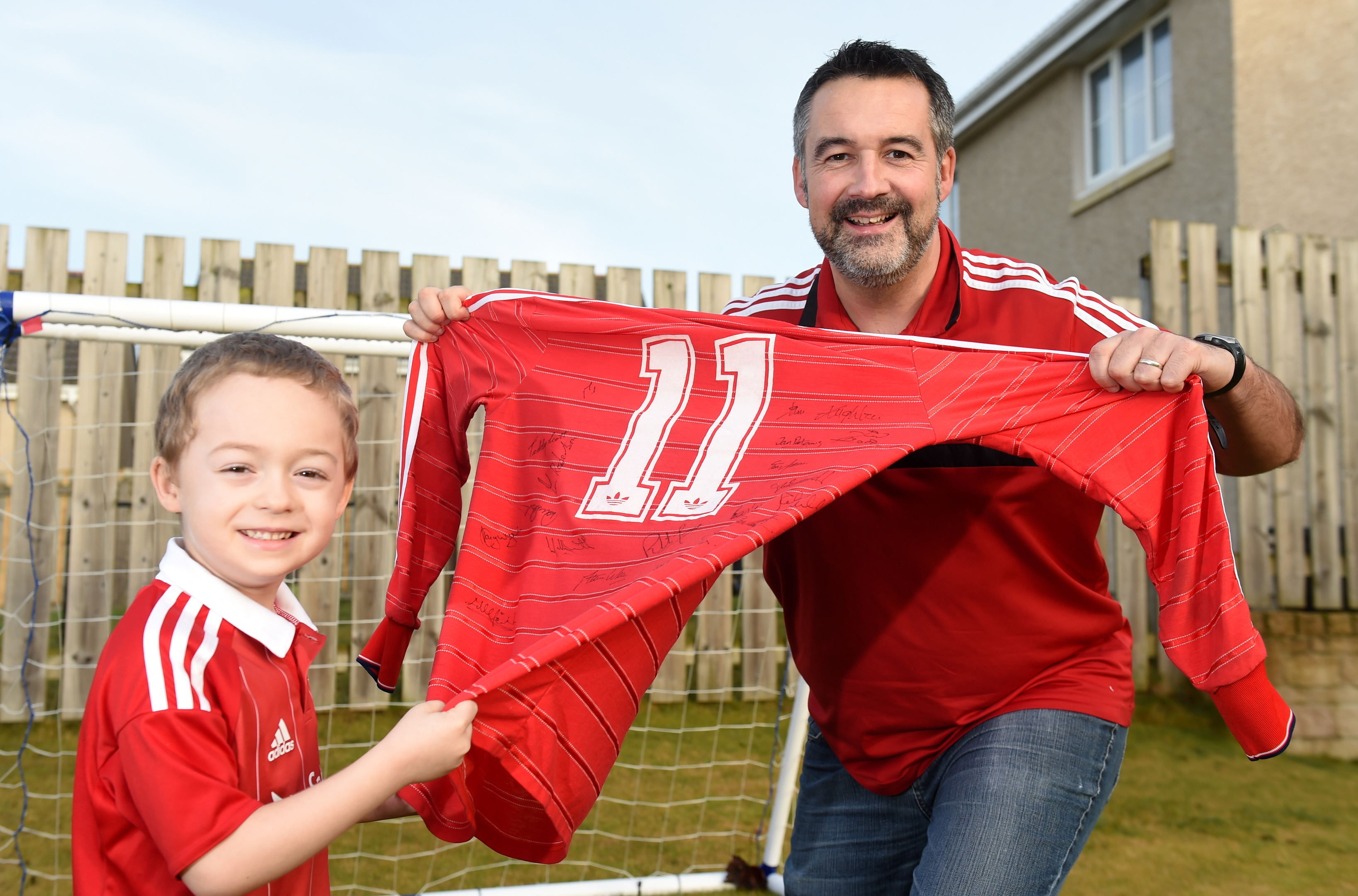Euan and son Cameron with Peter Weir's shirt from the match.
