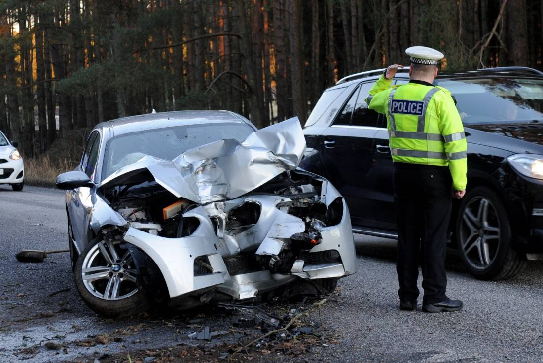 An officer directs traffic after the car hit a tree on A93 between Peterculter and Drumoak.