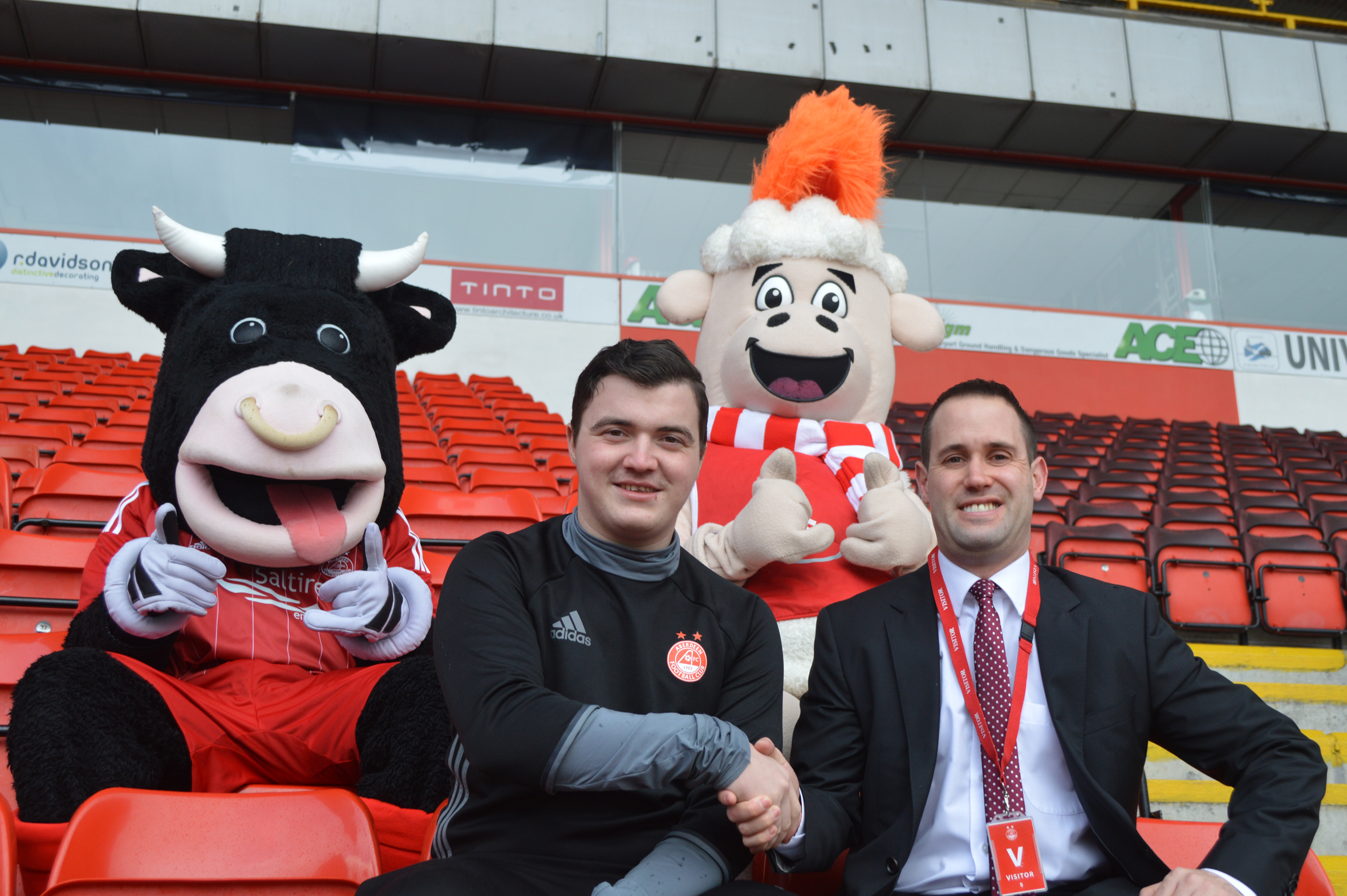 Russell Aitchison, right, with  Dean McBain of AFC and club mascots.