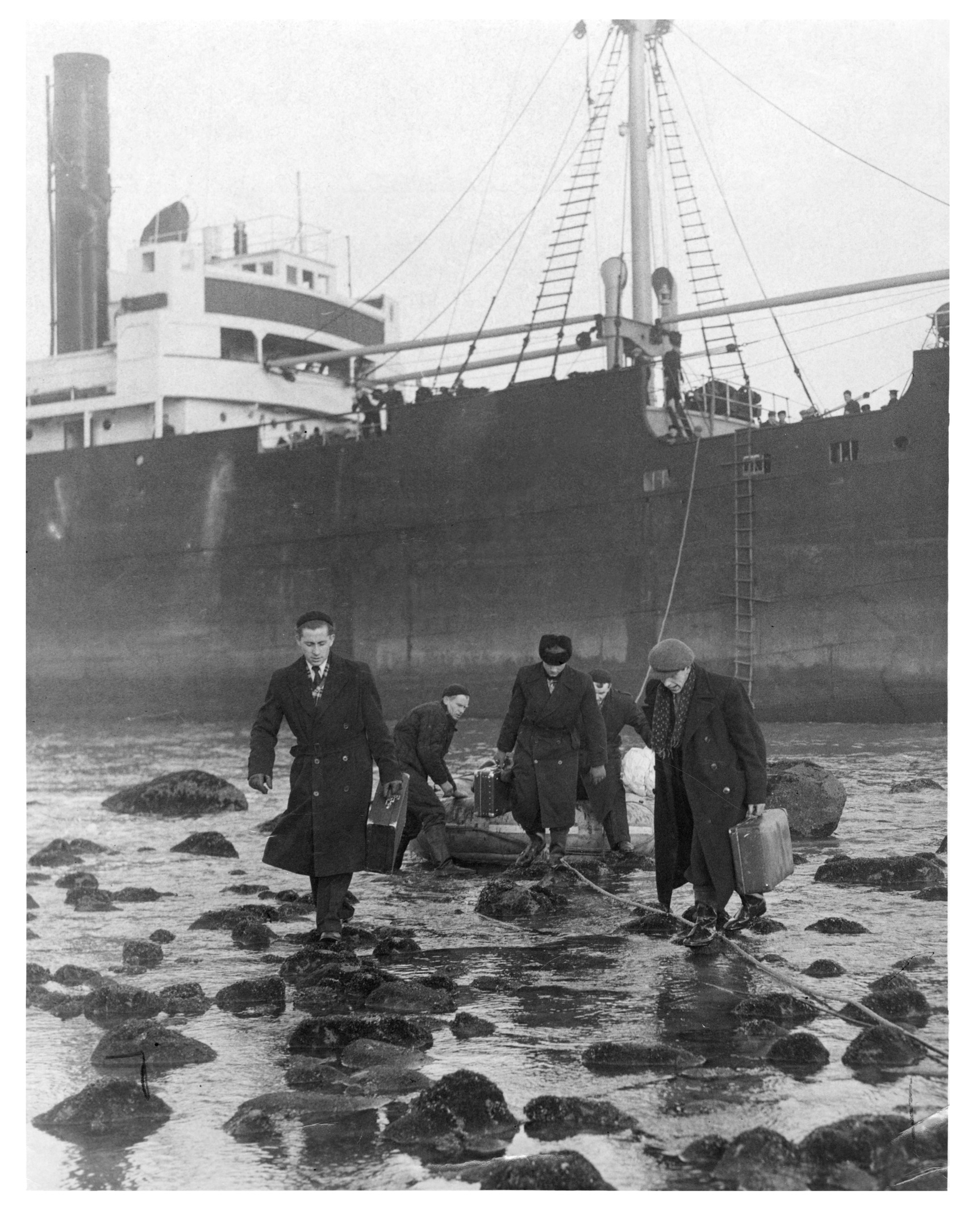 The crew of the grounded Russian steamer Krymov step from their rescue dinghy on to the beach at Murcar.