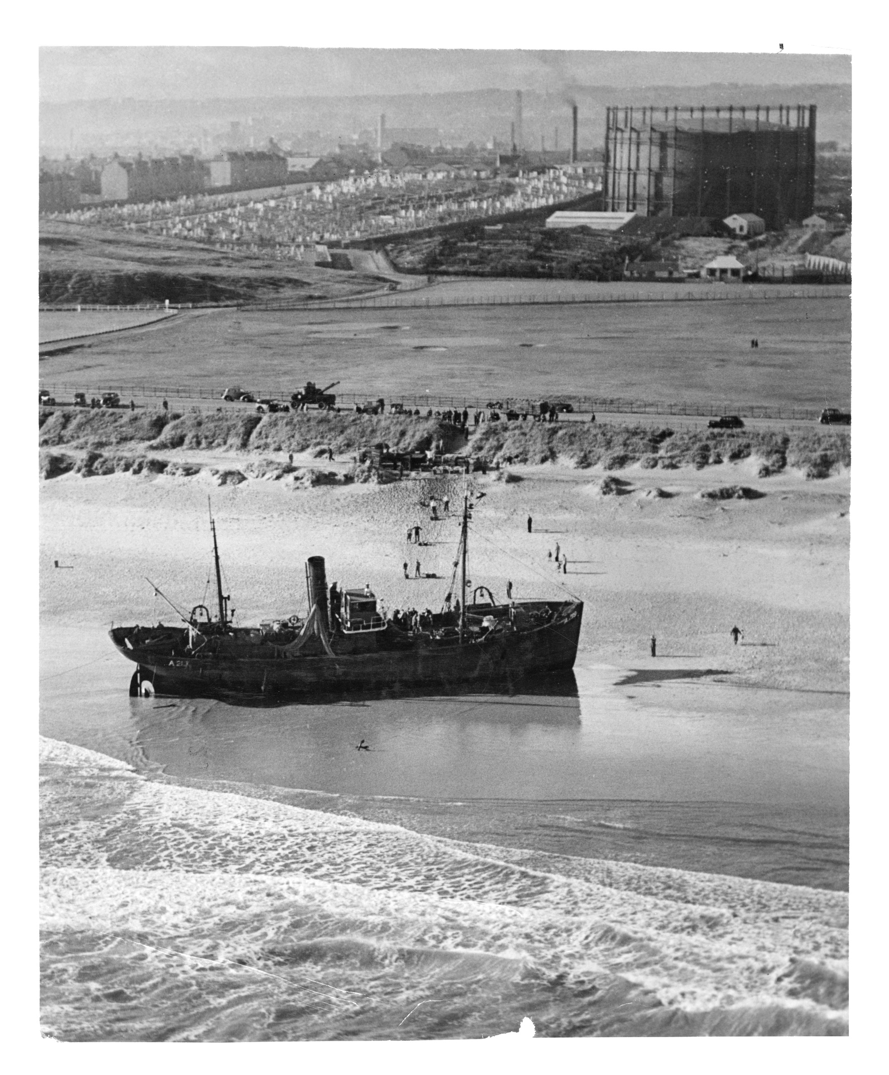 The crew of the Aberdeen trawler Sturdee, retrieving their catch from the beached boat.
