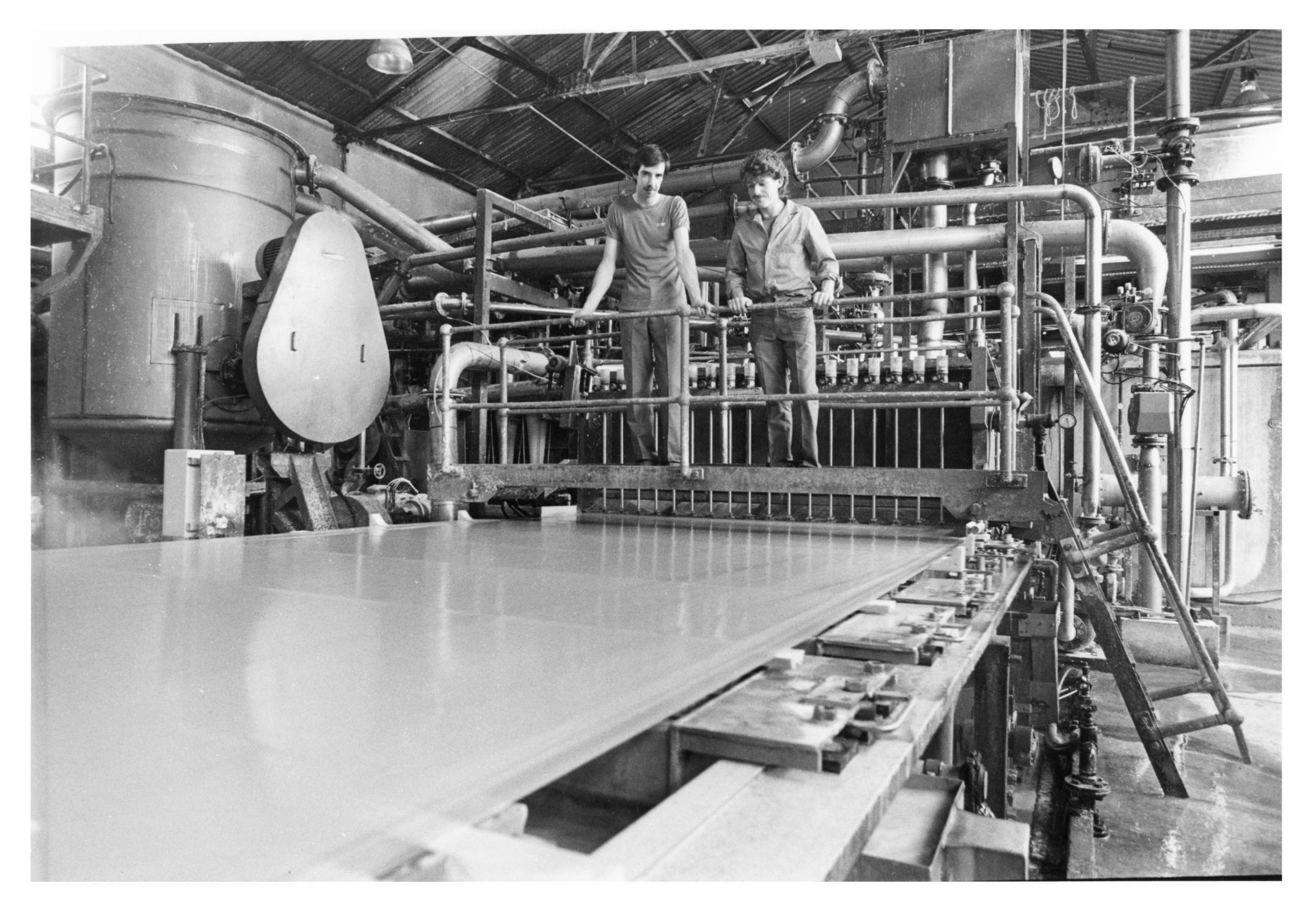 A drierman and machine assistant keep an eye on paper at the 'wet end' at Stoneywood Mill
