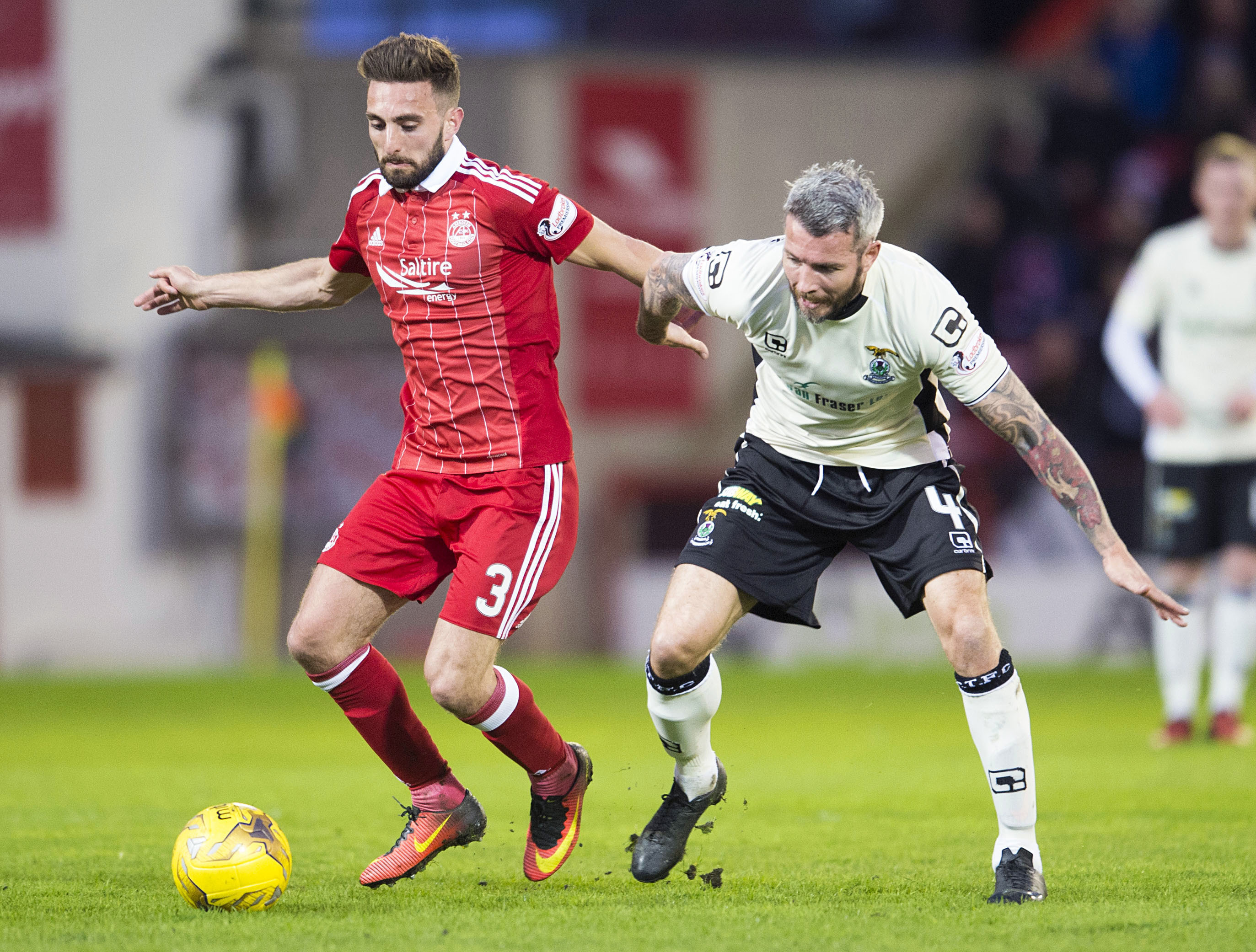 Aberdeen's Graeme Shinnie holds off Inverness' Kevin McNaughton (right).