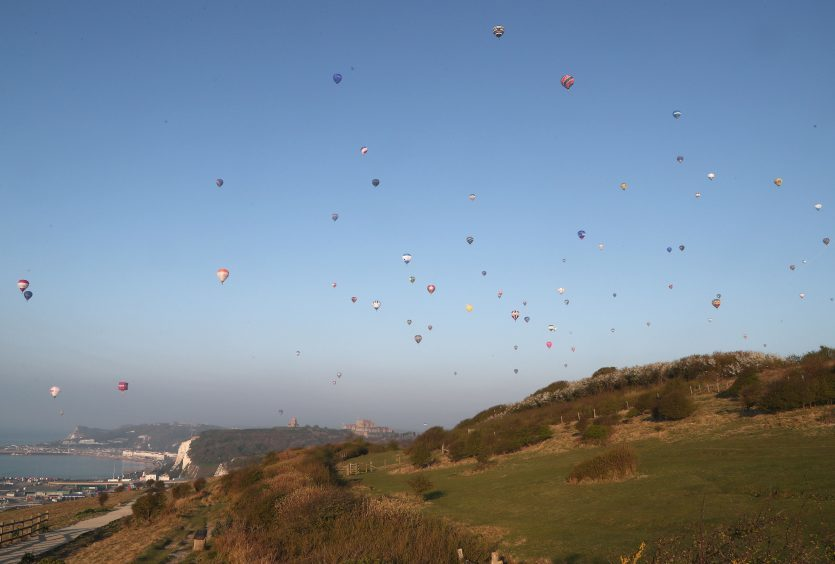 Some of the 100 balloons taking part in a World Record attempt for a mass hot air balloon crossing of the English Channel, fly over Dover in Kent. PRESS ASSOCIATION Photo. Picture date: Friday April 7, 2017. See PA story AIR Balloons. Photo credit should read: Gareth Fuller/PA Wire