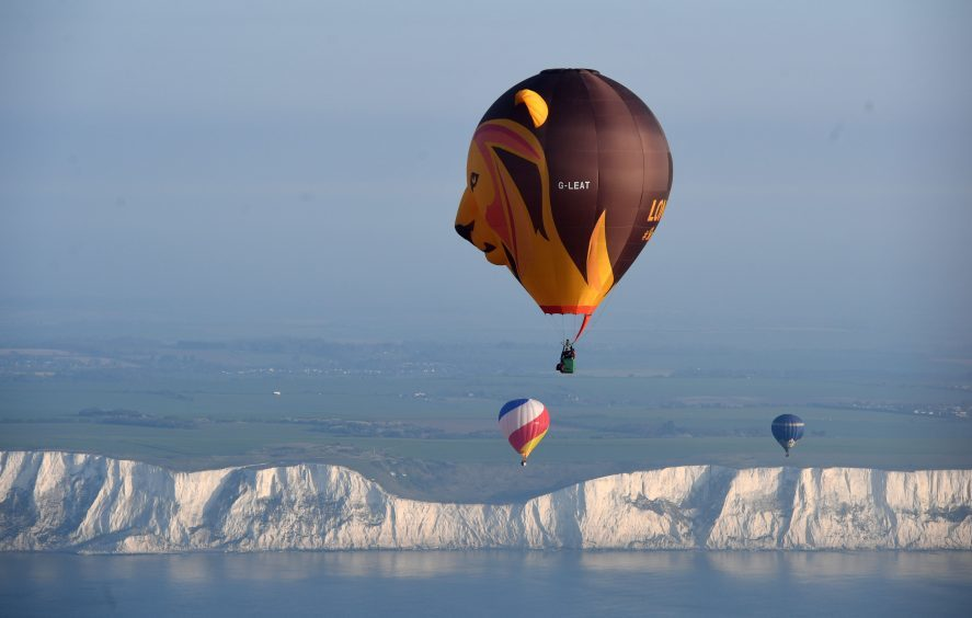 Some of the 100 balloons taking part in a World Record attempt for a mass hot air balloon crossing of the English Channel, fly over the White Cliffs of Dover in Kent. PRESS ASSOCIATION Photo. Picture date: Friday April 7, 2017. See PA story AIR Balloons. Photo credit should read: Victoria Jones/PA Wire