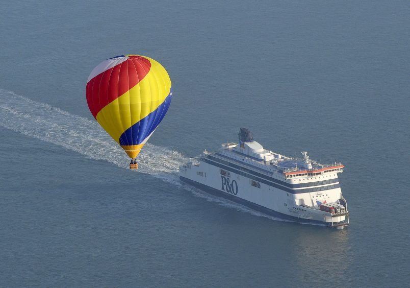 One of the 100 balloons taking part in a World Record attempt for a mass hot air balloon crossing of the English Channel, fly over the ferry close to Dover in Kent. PRESS ASSOCIATION Photo. Picture date: Friday April 7, 2017. See PA story AIR Balloons. Photo credit should read: Victoria Jones/PA Wire