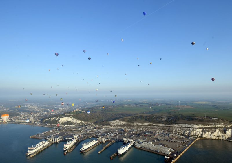 Some of the 100 balloons taking part in a World Record attempt for a mass hot air balloon crossing of the English Channel, fly over the Port of Dover in Kent. PRESS ASSOCIATION Photo. Picture date: Friday April 7, 2017. See PA story AIR Balloons. Photo credit should read: Victoria Jones/PA Wire