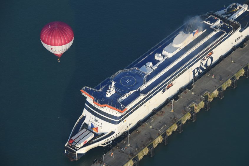 One of the 100 balloons taking part in a World Record attempt for a mass hot air balloon crossing of the English Channel, fly over the ferry in Dover in Kent. PRESS ASSOCIATION Photo. Picture date: Friday April 7, 2017. See PA story AIR Balloons. Photo credit should read: Victoria Jones/PA Wire