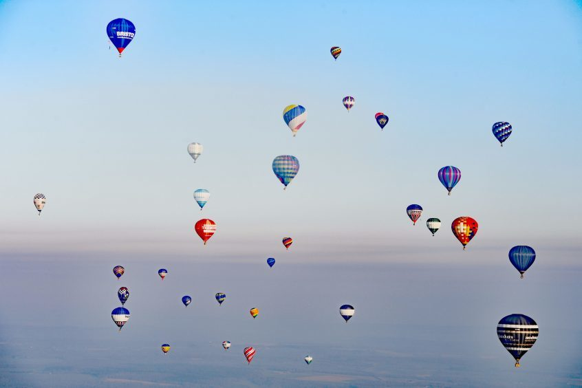 Some of the 100 balloons taking part in a World Record attempt for a mass hot air balloon crossing of the English Channel, fly over the coast close to Dover in Kent. PRESS ASSOCIATION Photo. Picture date: Friday April 7, 2017. See PA story AIR Balloons. Photo credit should read: Victoria Jones/PA Wire