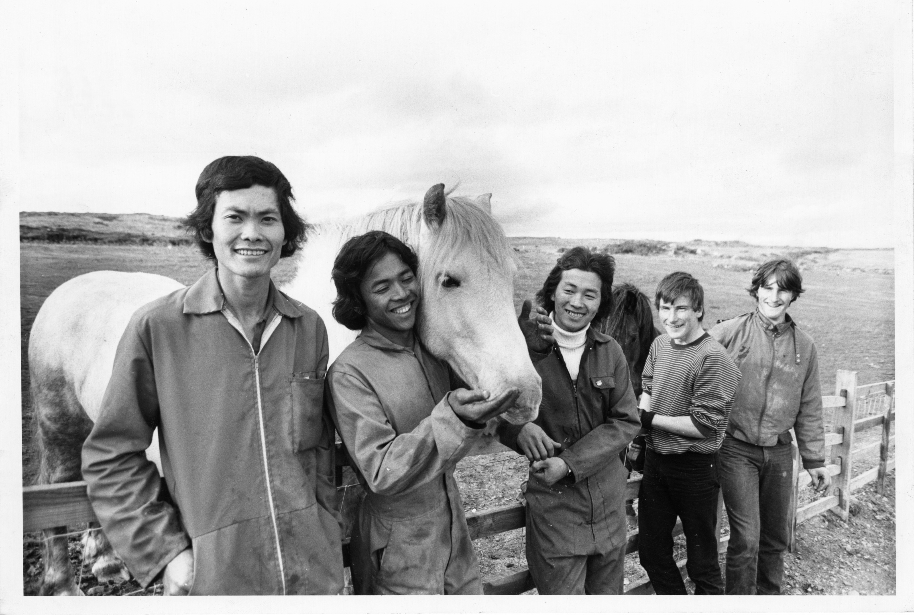 Vietnamese refugees and two local helpers pose with Doonies Farm horse Prince.