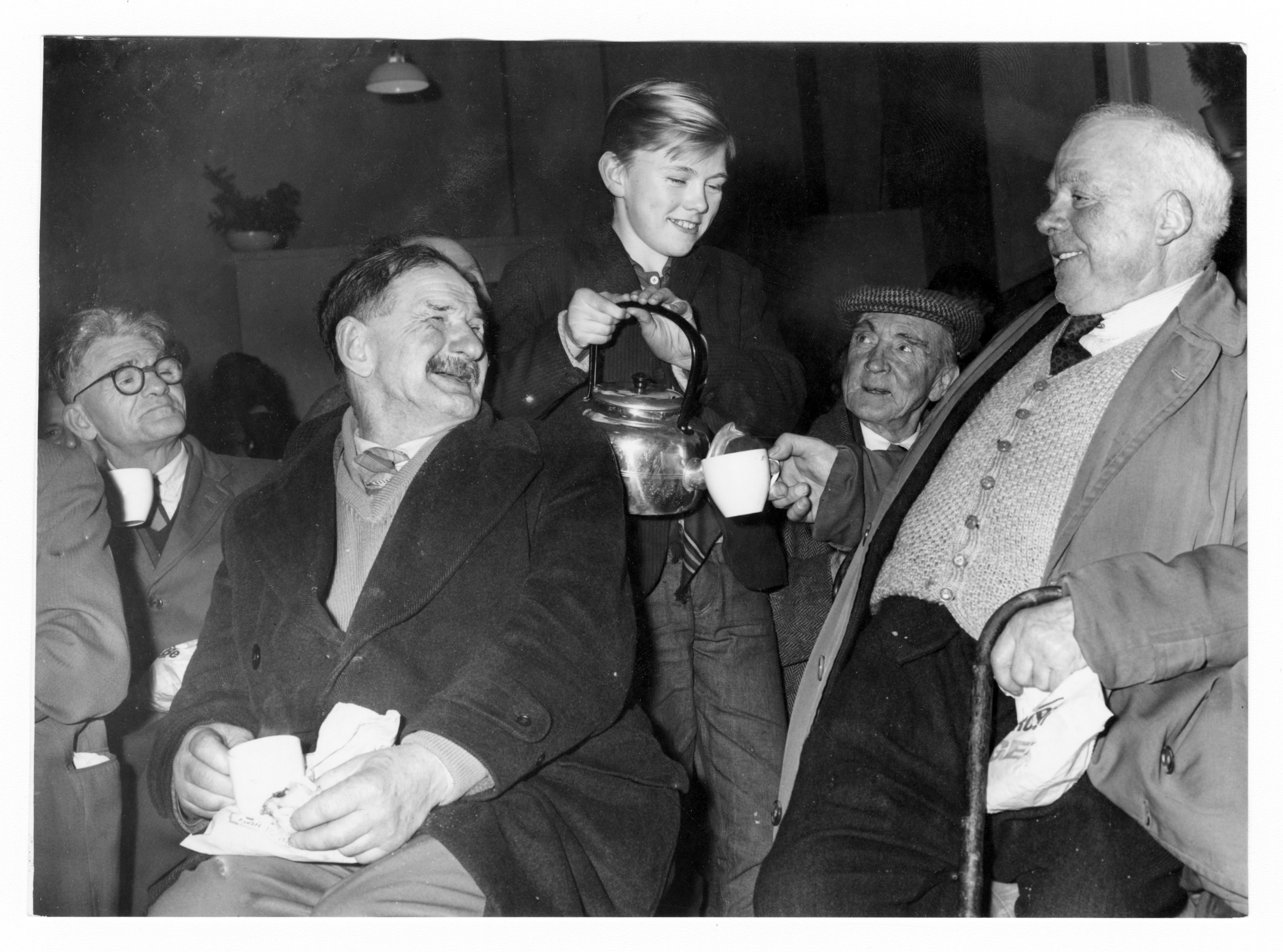 William Sutherland gets a refill from 15-year-old Norman Anderson at a Christmas party at the Shiprow Tavern.