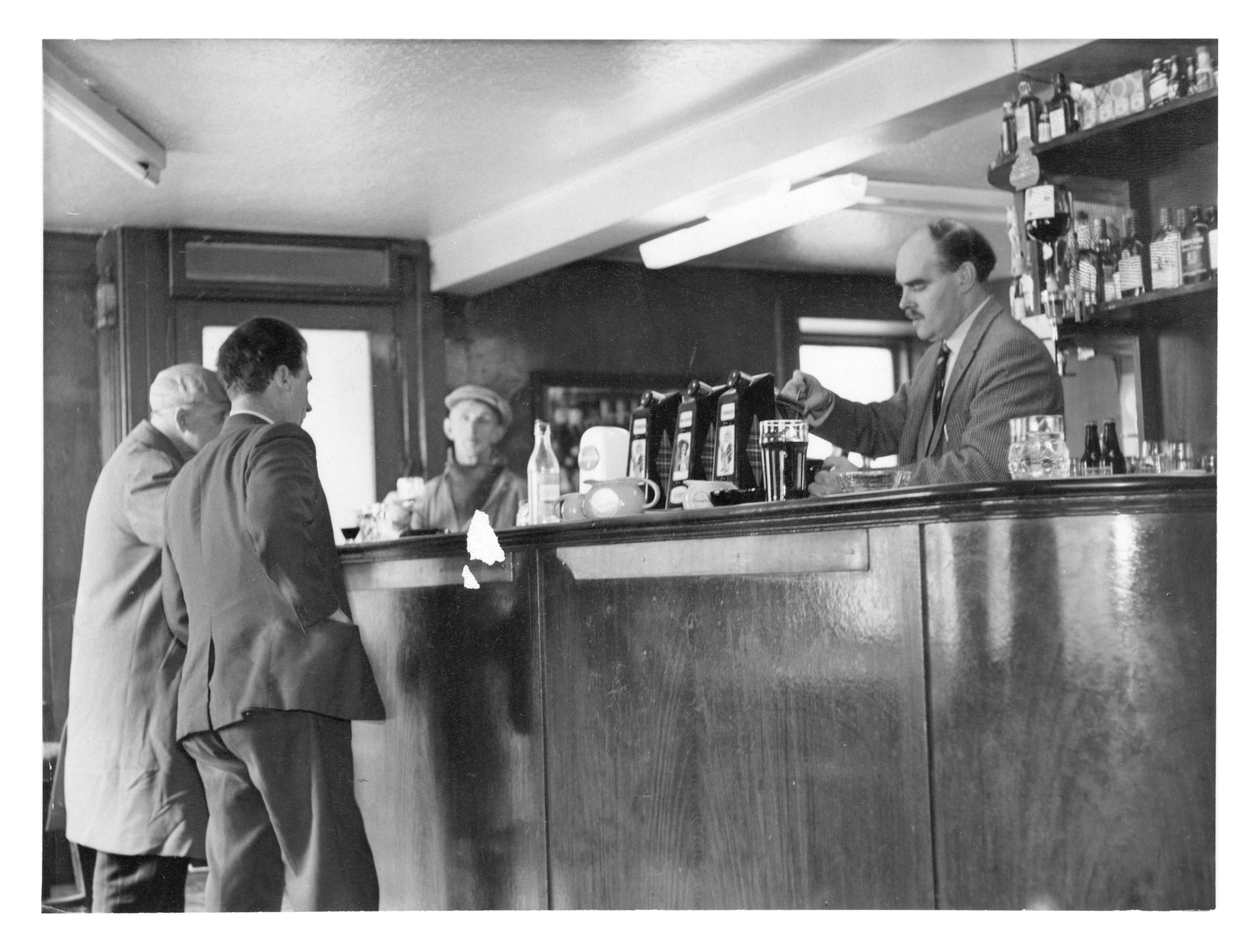 The owner of the St Clement's Bar, William Johnston, pours a pint for a customer in 1965.