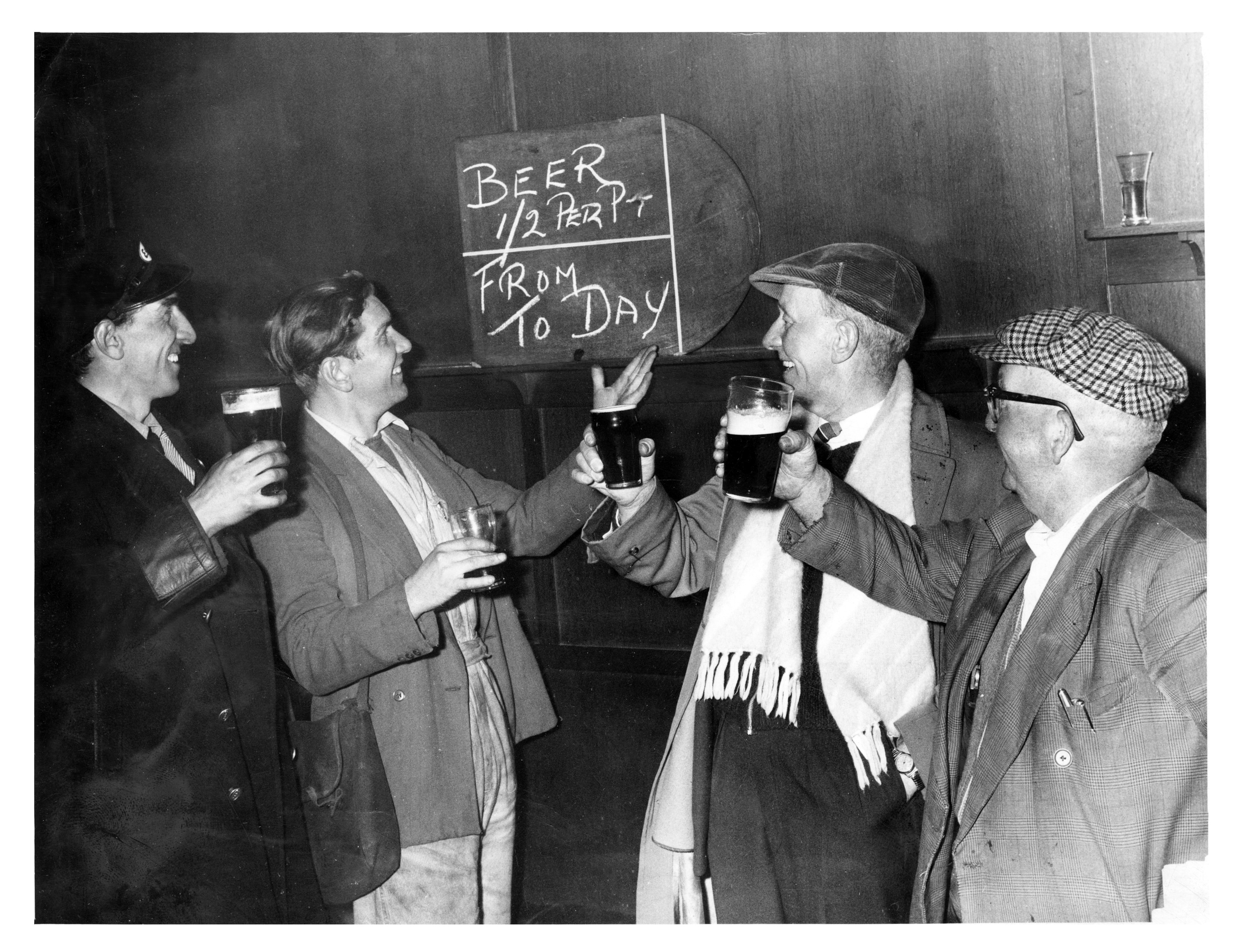 Customers at the City Bar raise their glasses to the new price for a pint of beer.