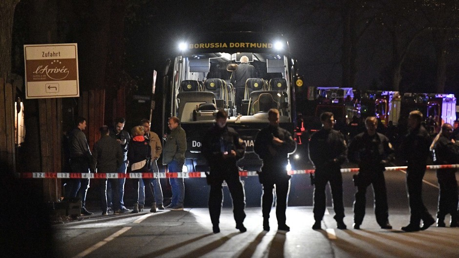 Police officers stand in front of Borussia Dortmund's damaged team bus after an explosion before the Champions League match against Monaco (AP Photo/Martin Meissner)