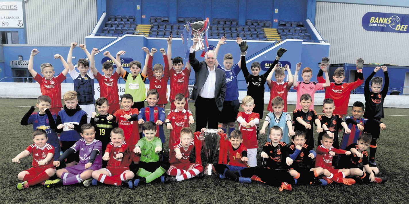 Craig Brown hoists the Premiership trophy with a group of children as part of the SPFL Trust's Trusted Trophy Tour. (Picture by Chris Sumner.)