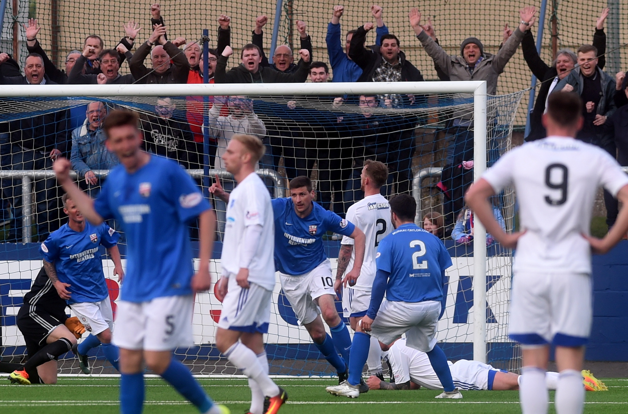 Chris Templeman (blue 10, centre) celebrates Montrose's equaliser as Peterhead were held to a 1-1 draw. (Picture by Darrell Benns.)