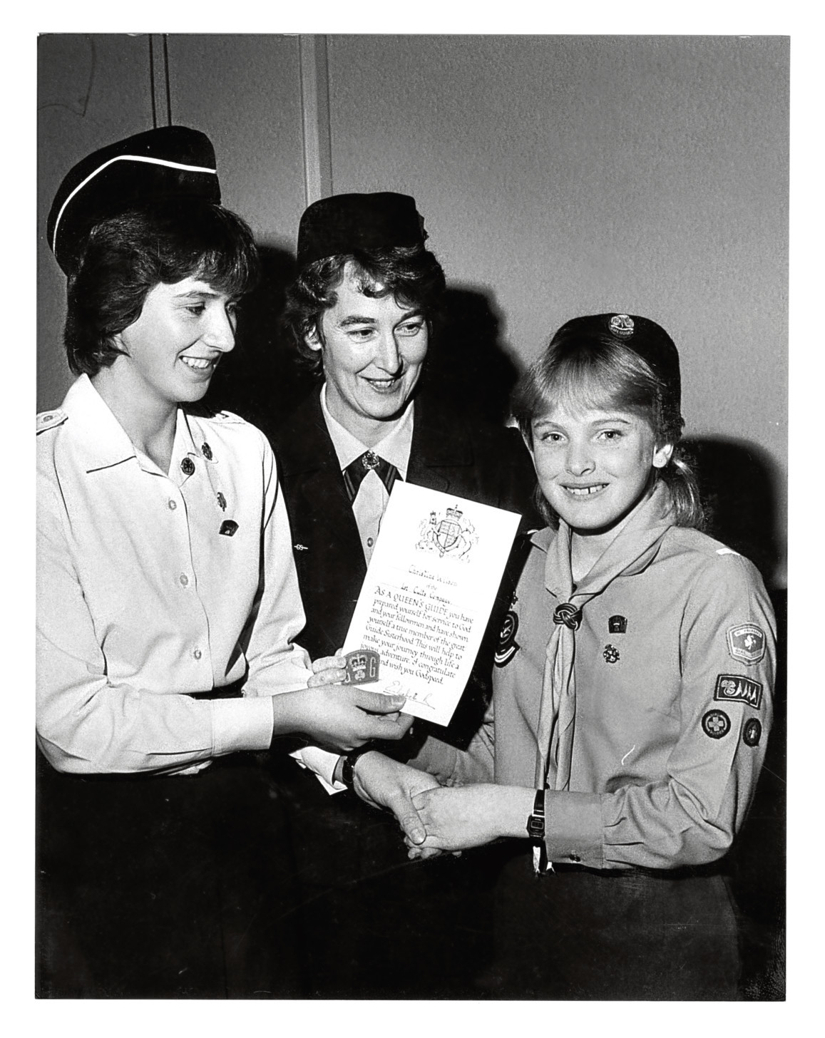 1983: Patrol leader Christine Wilson, right, 1st Cults Guides, receives the Queen's Guide Award from Young Leader Colette McFarlane as Guider Mrs Morag Williamson looks on.