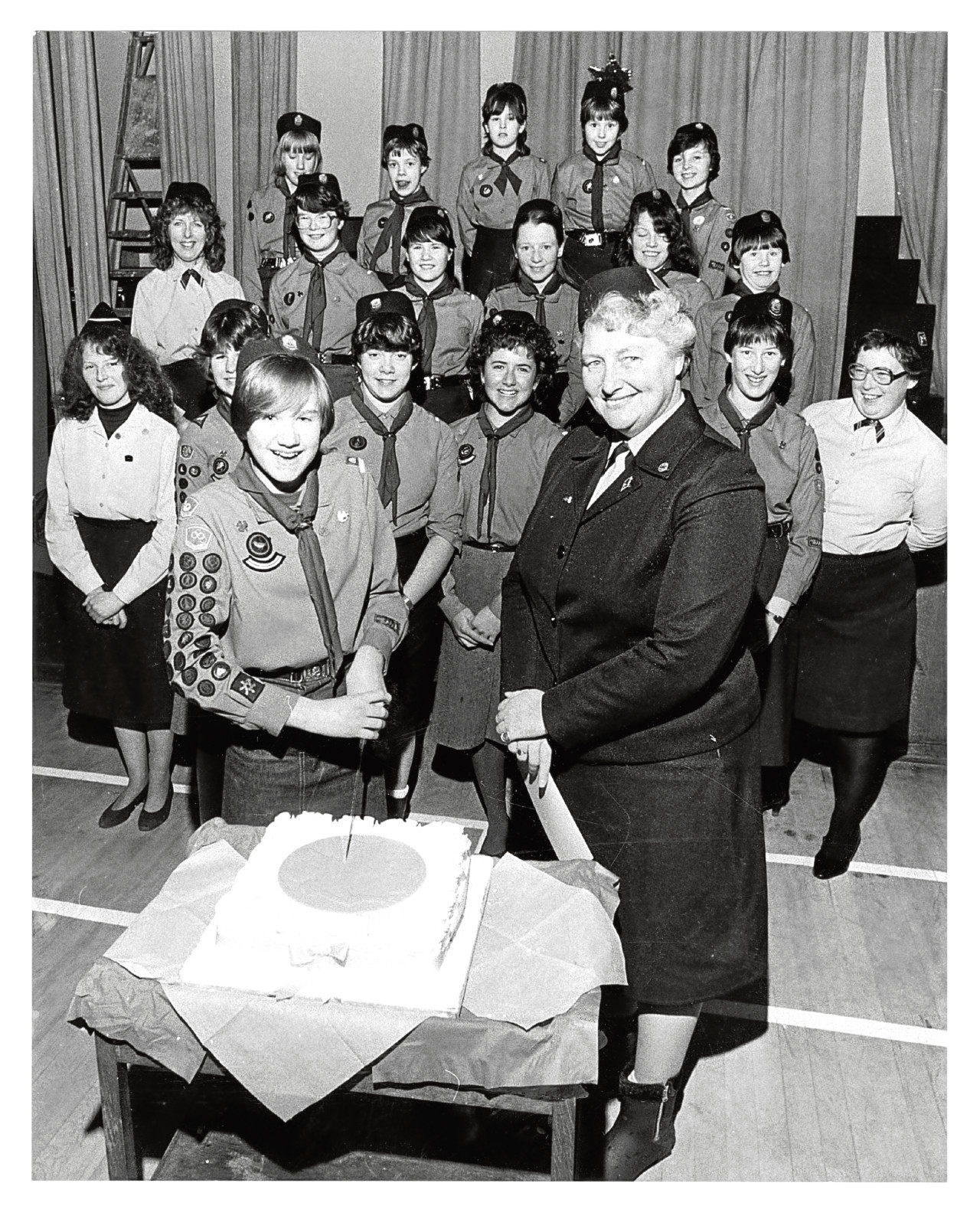 1984: Patrol leader Tracy Smith cuts her celebration cake after District Commisioner Jean Park presented her with her Queen's Guide certificate  at the 39th Queen's Cross Church Guides meeting.