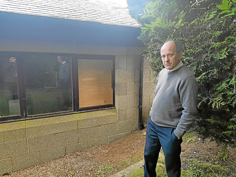 Reverend Hugh Wallace and the damage at Newhills Parish Church.