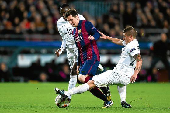 Lionel Messi of FC Barcelona competes for the ball with Blaise Matuidi (L) and Marco Verratti of PSG.