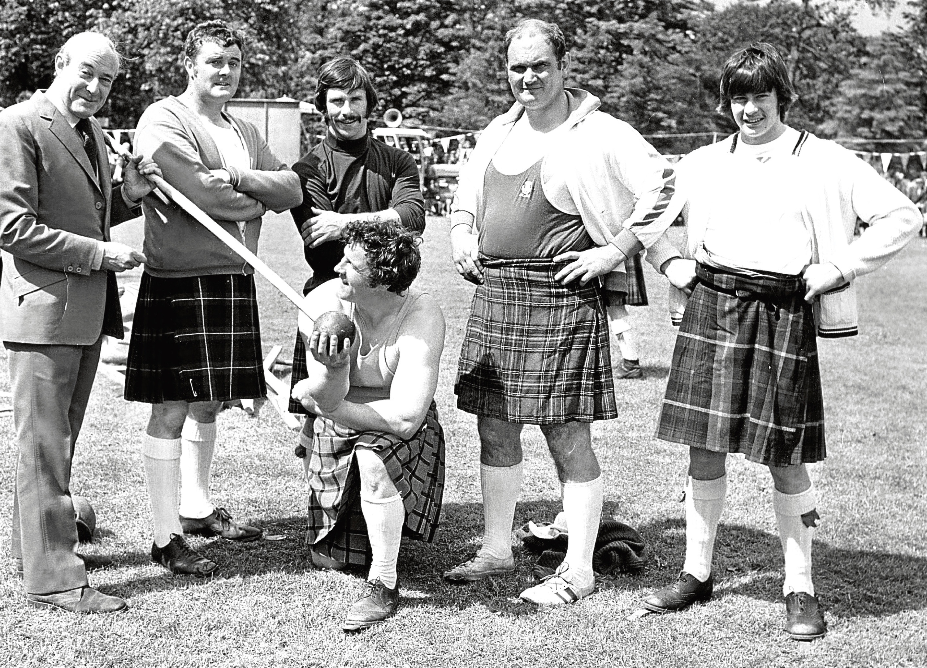 Former BBC newscaster Robert Dougall tests the weight of the heavy hammer with the help of heavy Charlie Allan, along with other heavies Ed Weighton, Colin Scott, Doug Edmonds and Murray Brown.