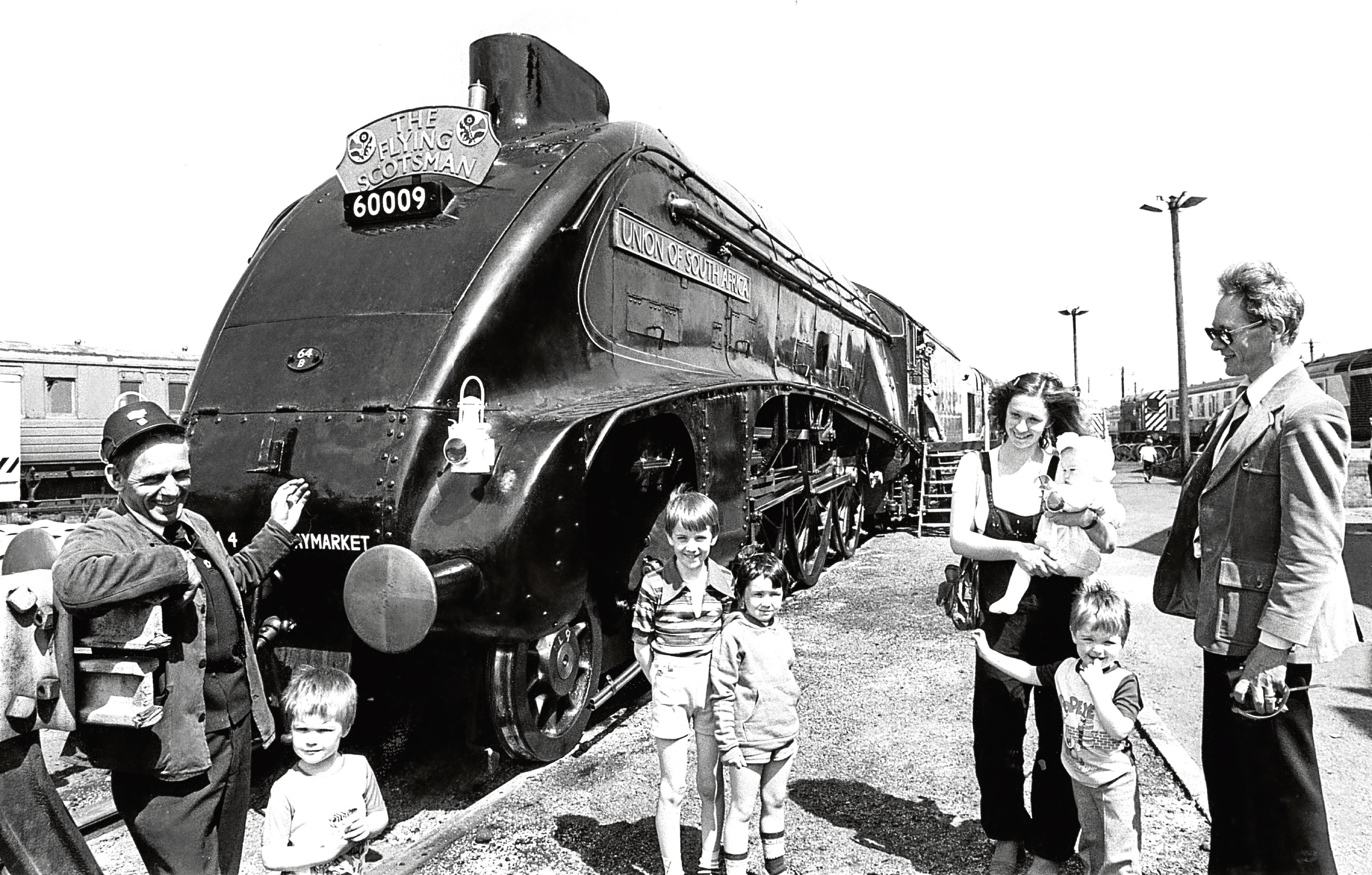 Train driver at the Ferryhill depot Angus Cameron shows off the Flying Scotsman to, from left, Matthew Smith, 3, Graham, 8, and Marion Mitchell,5, Patricia Smith with baby Rachel, and Daniel Smith, 3.