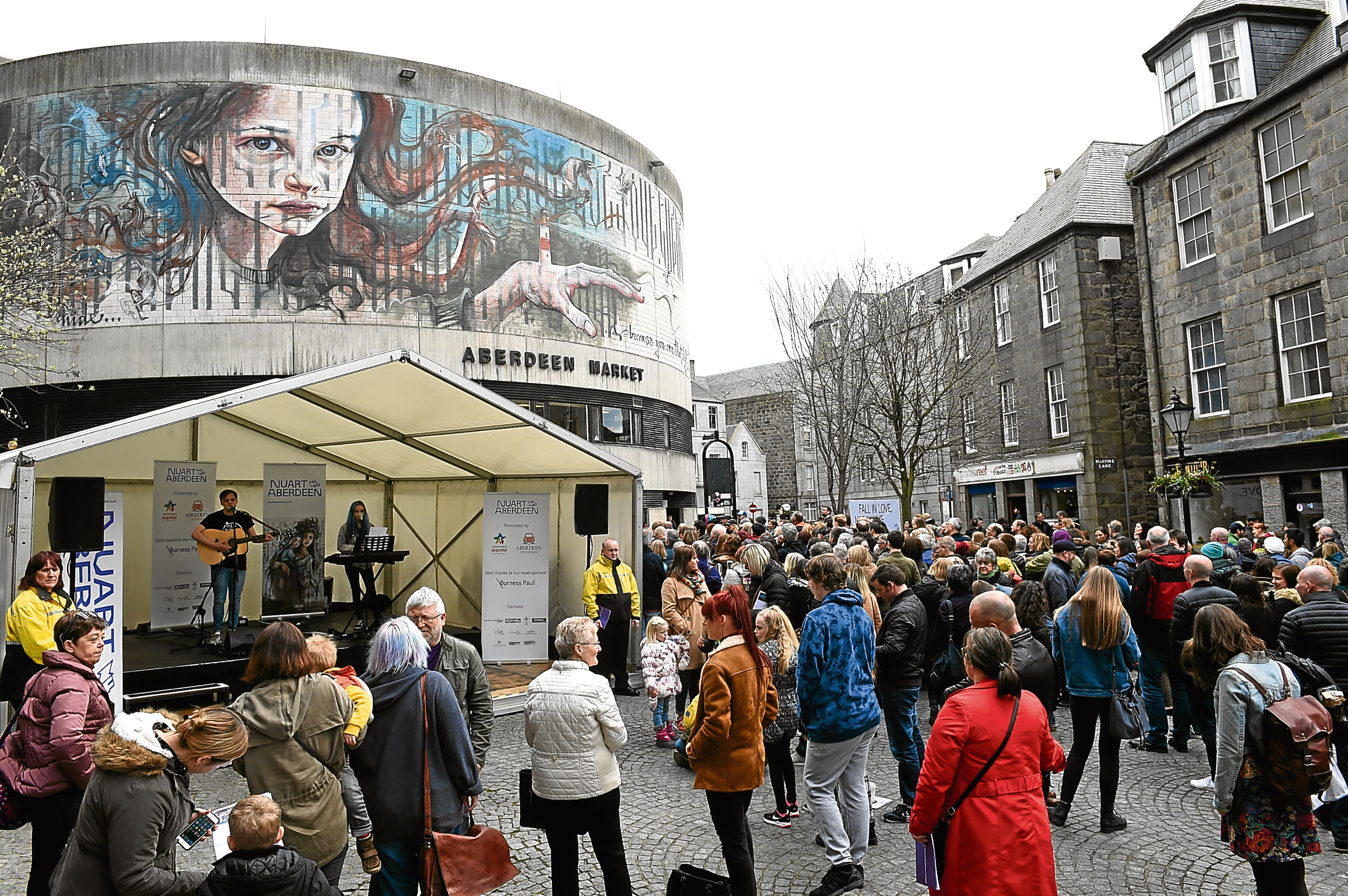 Crowds stand in front of one of the Nuart Festival art works.