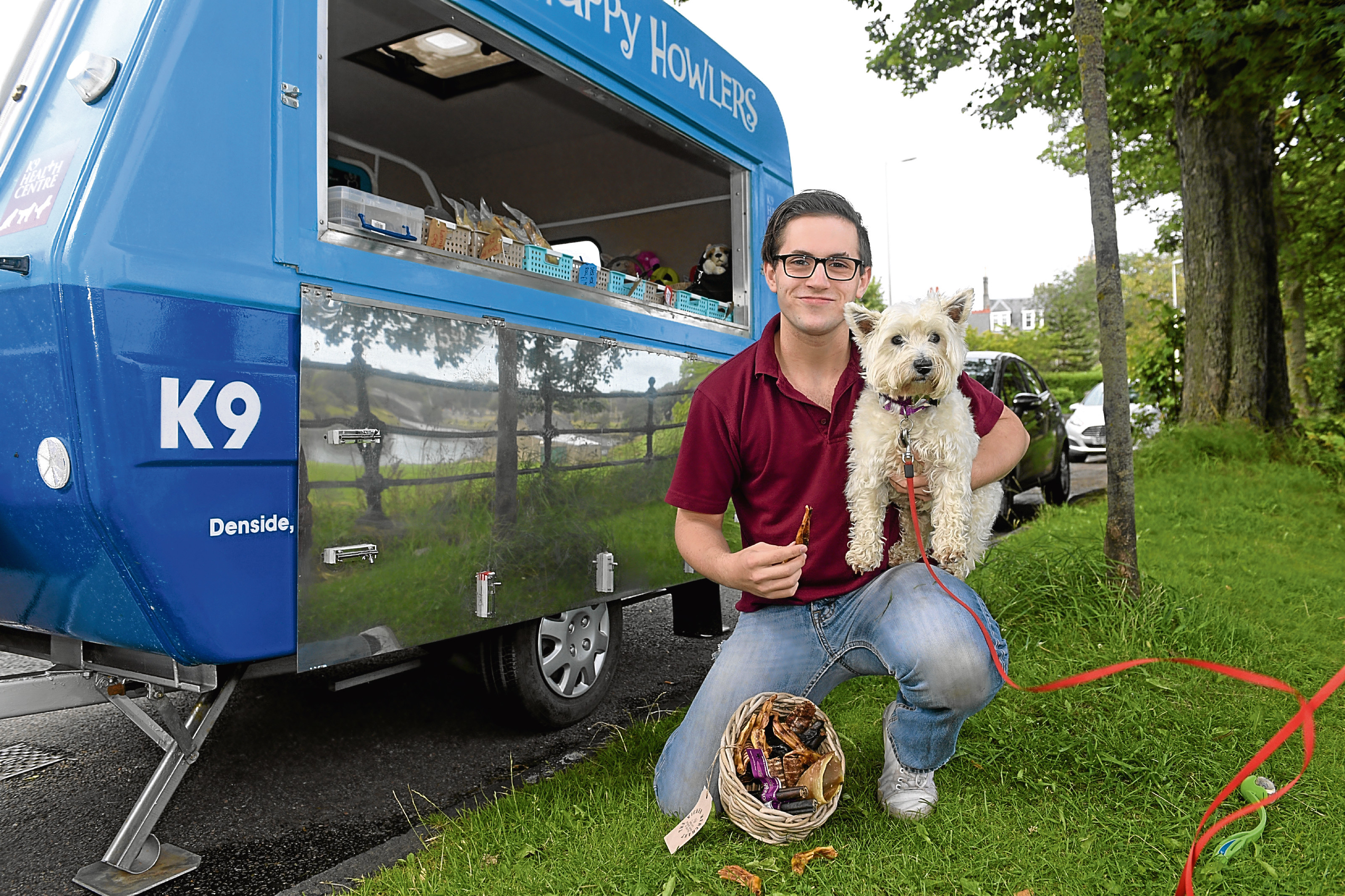West Highland Terrier Pyper tries some of the treats on offer from Samuel at the deli van.
