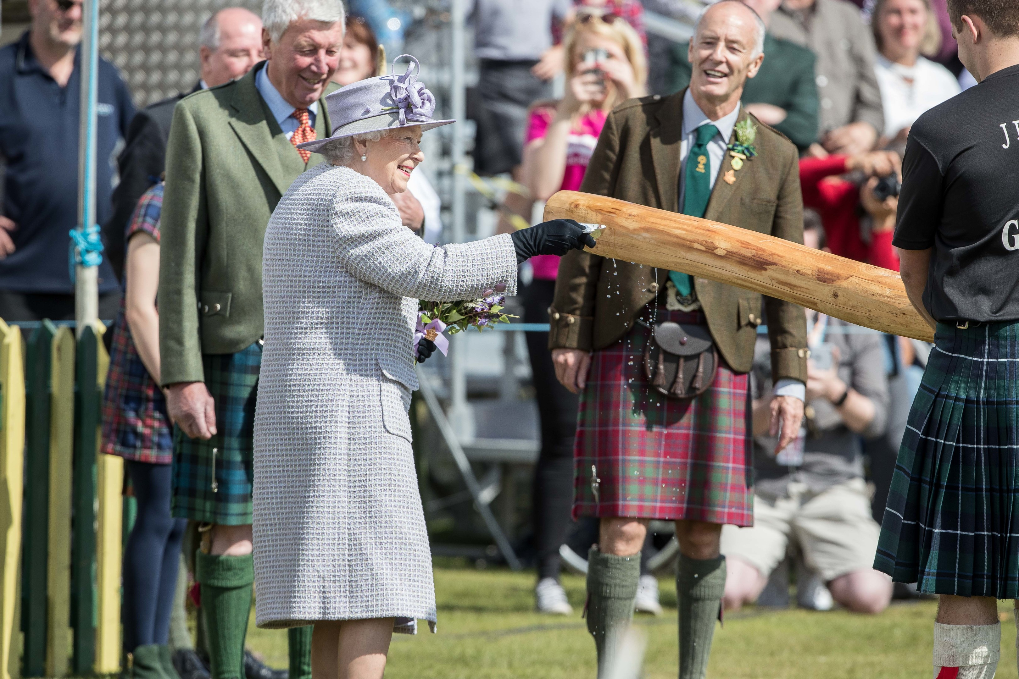 Her Majesty pouring whisky over a new games caber.  Pic Derek Ironside / Newsline Media