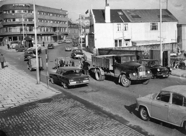 1963: Workmen busy working at the junction of Clifton Road, Powis Terrace and Great Northern Road in Aberdeen, in February 1963 cause a bit of a traffic jam outside the Northern Hotel.