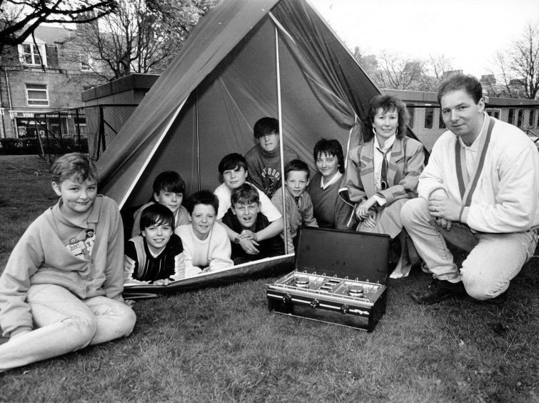 1988: Chevron HR representative Trish Will presents Fersands and Fountain Urban Aid project's Ian Armstrong with a tent and camping stove, bought with a £150 donation made by the oil company. Looking on are some of the project members.