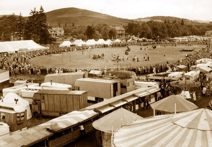 1963: A large crowd watches the field events at the Aboyne Highland Games in August, 1963, on what would appear to be a cold, wet day judging by the amount of people wearing waterproofs. This year's games are on Saturday, August 2.