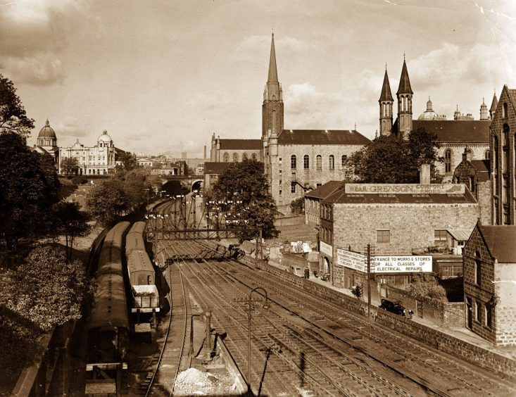 1954: Looking along the Denburn from Aberdeen's Union Bridge towards the Triple Kirks and HM Theatre in October, 1954. An array of railway signals straddles the then busy railway lines with a siding on the left next to Union Terrace Gardens.
