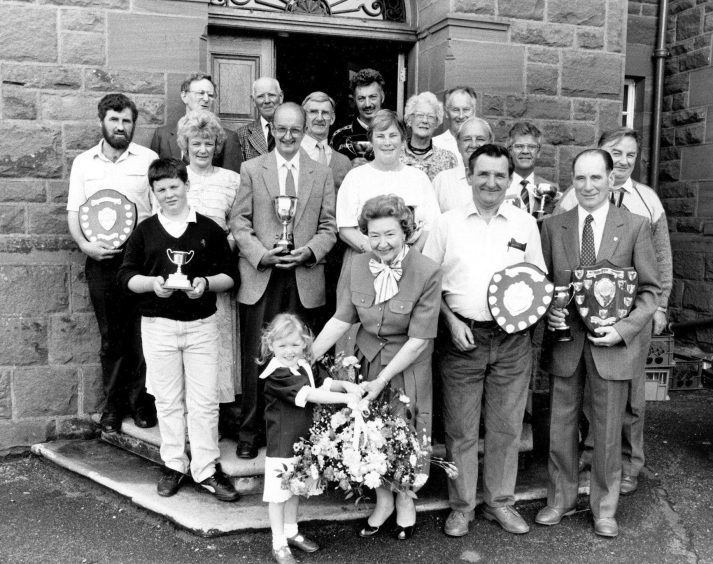 1990: Receiving a lovely floral arrangement from four-year-old Siobhan Aboyne - watched by winners from the Aberdeen Allotments and Gardens Society show - is Anne Cocker, who presented trophies at the event.