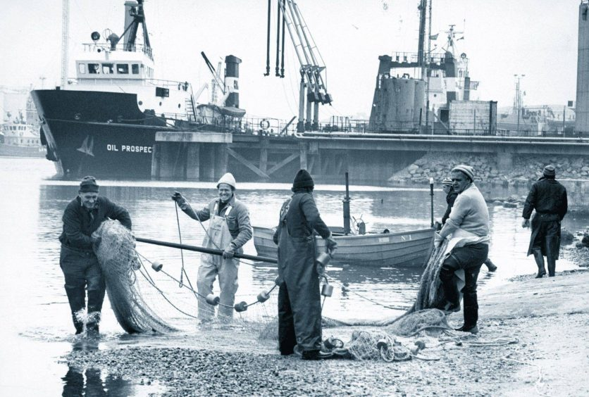 1978: The old and the new merge in this picture from April 1978 at the River Dee downstream of the Victoria Bridge, Torry, as salmon fishers haul in their nets against the background of oil industry supply vessel Oil Prospector.