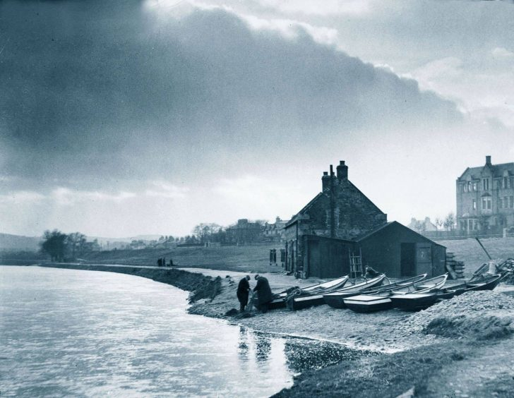 Salmon fishers at work tending their nets in late afternoon at the bothy by the River Dee on Riverside Drive, Aberdeen, in 1936.