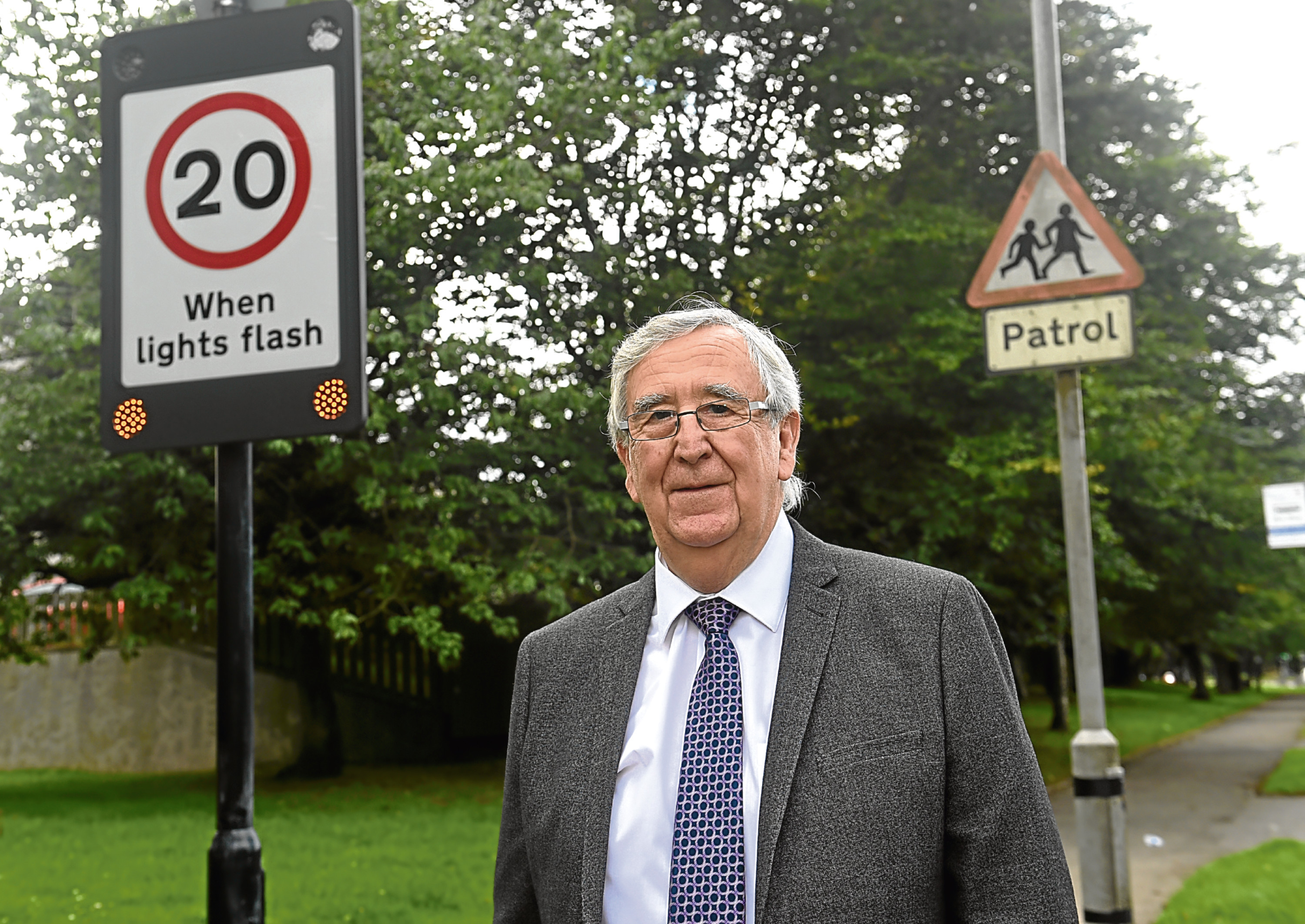 The 20mph sign outside Glashieburn Primary School has not been working properly for some time now and councillor wants to urge drivers to check their speed around the school.  Pictured is Councillor John Reynolds. Picture by HEATHER FOWLIE
