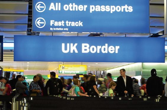 """File photo dated 22/07/15 of passengers going through the UK Border at Terminal 2 of Heathrow Airport. Government plans to cut immigration to the UK to less than 100,000 have been defended by a leading member of Theresa May's Cabinet. PRESS ASSOCIATION Photo. Issue date: Thursday August 10, 2017. First Secretary of State Damian Green made clear ministers believe a """"sustainable level"""" of immigration would be for the number of people coming to the UK to be in """"the tens of thousands"""". See PA story POLITICS Immigration. Photo credit should read: Steve Parsons/PA Wire"""