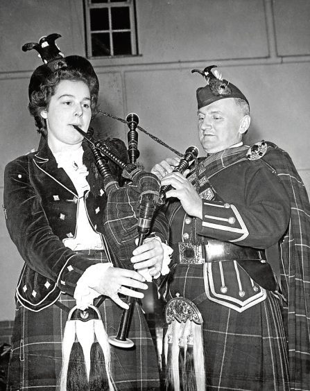 1955: Pipe Major G Hepburn, of Turriff Pipe Band, helps Miss Elma Reid with the tuning of the pipes.