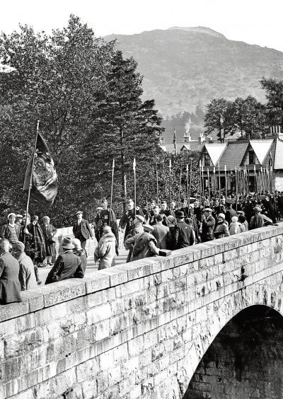 1928: Clan Duff cross the Bridge of Cluny during the march of the clans in this atmospheric photo.