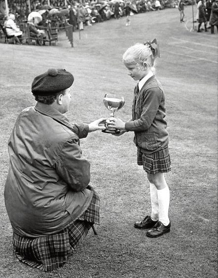 1974: Seven-year-old Braemar youngster Dianne Wright received a trophy from the Duke of Fife for dancing.