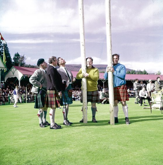 1971: Judges and competitors get ready for the iconic tossing the caber contest, a highlight of any games.