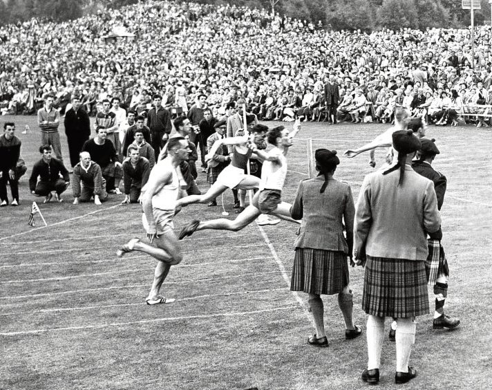 1960: Crowds gather to watch the runners crossing the line during the 100 yards sprint.