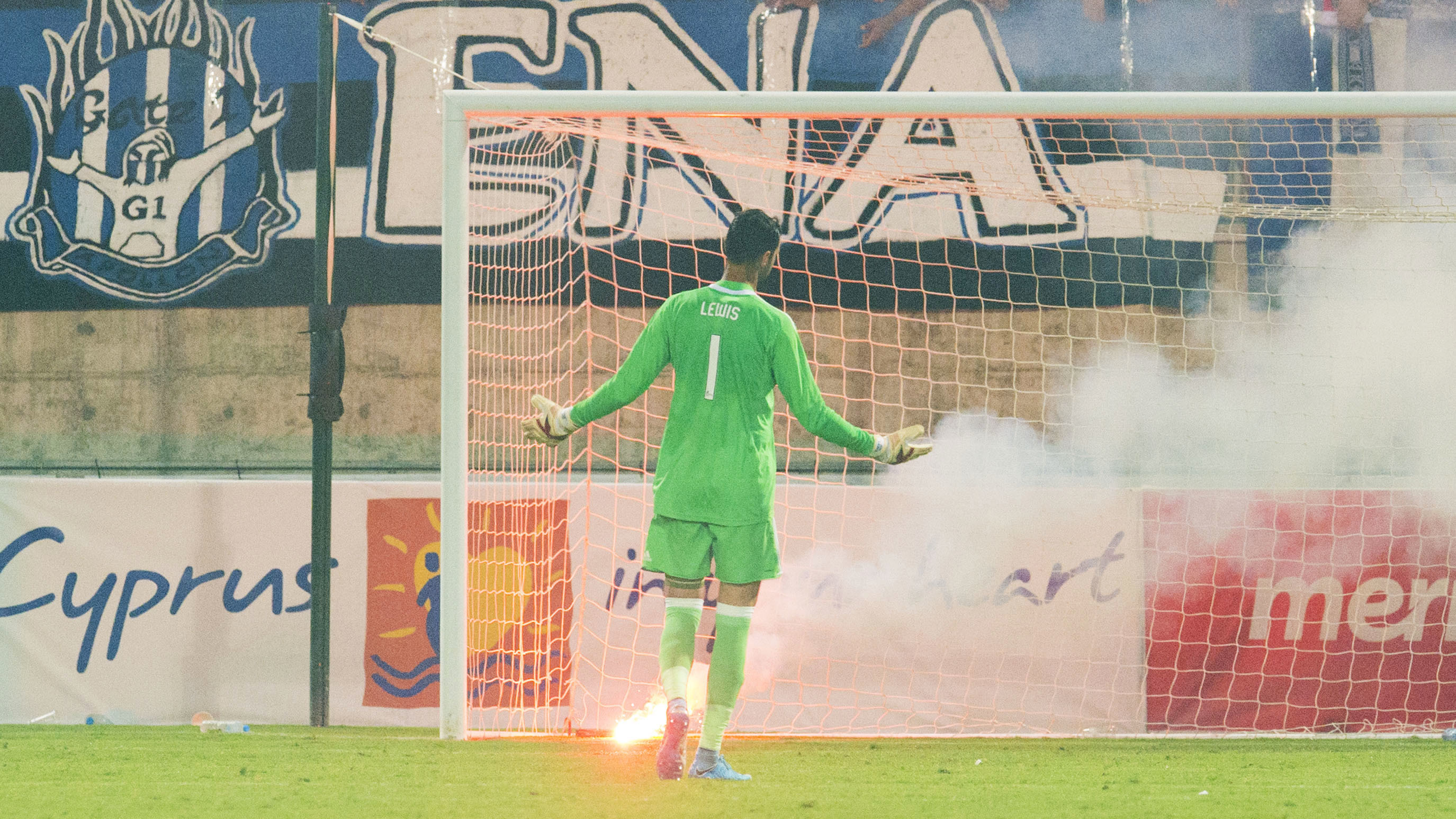 Aberdeen goalkeeper Joe Lewis in action while a flare is on the pitch.